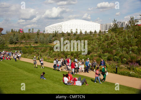 People sitting on lawns in sunshine on a sunny day with Basketball Arena at Olympic Park, London 2012 Olympic Games - Stock Image