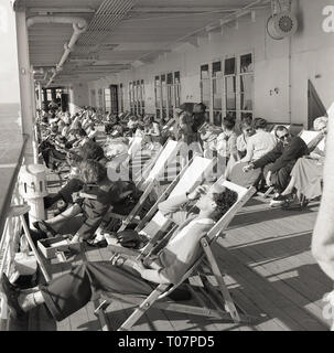 1950s, on a steamship passengers relax in deckchairs on the ships' deck. - Stock Image