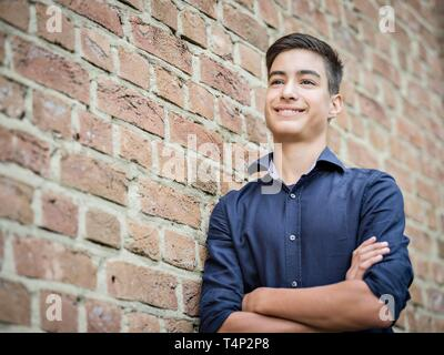 Boy, teenager, 14 years, standing and smiling on the wall, portrait, Germany - Stock Image
