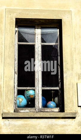 An abundance of globes can be glimpsed through the crumbling windows of an old government office building in Fivizzano, Tuscany, Italy. - Stock Image