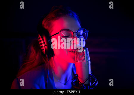A young woman in glasses singing by the microphone - Stock Image