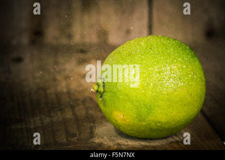 Fresh lime close up with drops of water on an old wooden table. - Stock Image