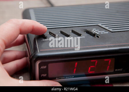 Pushing the sleep or snooze button on an old analog alarm clock - Stock Image