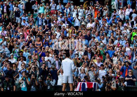 London, UK. 14th July 2019. Wimbledon Tennis Tournament, Day 13, mens singles final; Novak Djokovic (SER) has his photograph taken by photographers and the crowd with the Wimbledon mens singles final trophy Credit: Action Plus Sports Images/Alamy Live News - Stock Image