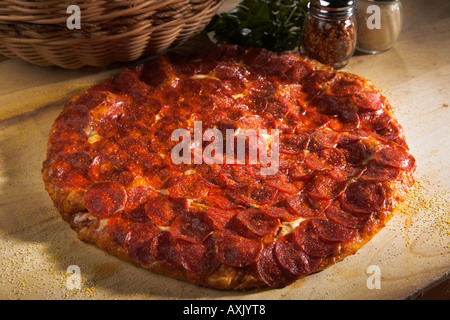 baked pepperoni meat pizza with cheese sauce bred crust brown on wood cutting board next to basket tomatoes powder shaker - Stock Image