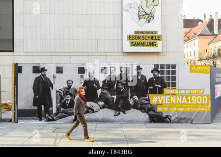 Vienna Secession, view of a middle aged woman walking past a Leopold Museum advertisement celebrating artists of the Secession movement in Vienna. - Stock Image