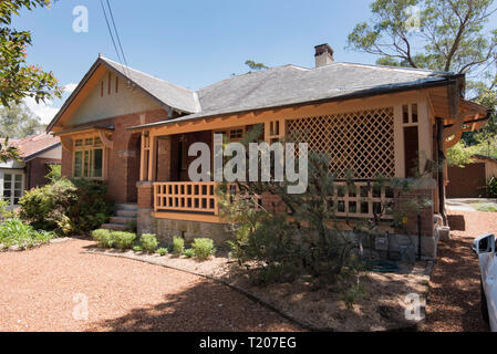 An Australian brick and slate roof federation home with a return front veranda and a well kept front yard and garden in Sydney - Stock Image