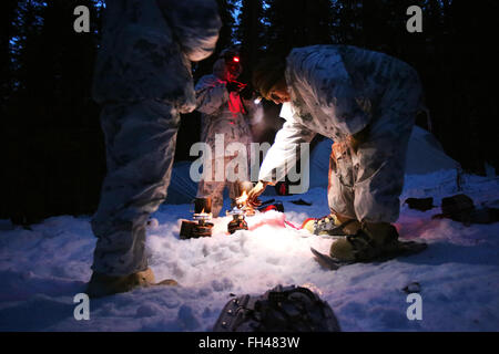 A group of U.S. Marines  assigned to The Combined Arms Company out of Bulgaria uses small burners to melt snow into - Stock Image
