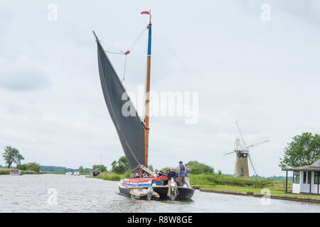 Wherry, traditional sailing boat on Norfolk Broads, River Thurne, in front of St Benet's Level Drainage Mill. June. - Stock Image