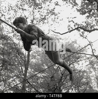 1960s, historical, a young adventure scout using his hands and legs on a rope to manouver himself across a clearing between two trees, England, UK. - Stock Image