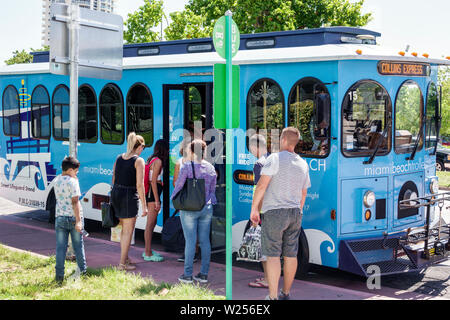 Miami Beach Florida North Beach free Trolley bus stop man woman boy passenger boarding public transportation Collins Express - Stock Image
