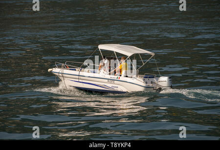LAKE GARDA, ITALY - SEPTEMBER 2018: Family on a small boat with outboard motor on Lake Garda. - Stock Image