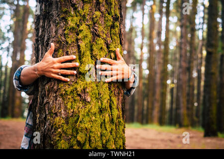 Ecology and environment concept with caucasian people woman hugging a green tree in the outdoor forest - nature and eco lifestyle - change the world - - Stock Image