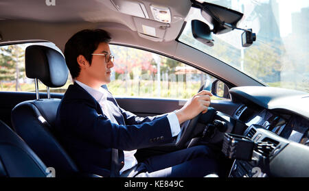 Side view portrait of businessman driving car - Stock Image