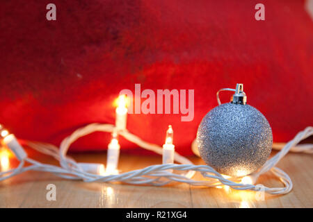 Festive holiday scene with copy space, showing white twinkly lights and sparkly silver ball - Stock Image