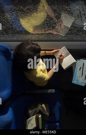 young woman loking in diary book and writing travel blog train during traveling in train near window - Stock Image