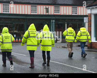 Ashbourne Shrovetide Football 2019. Game marshals in high vis jackets patrol the streets of the historic town prior to the Ash Wednesday match. - Stock Image