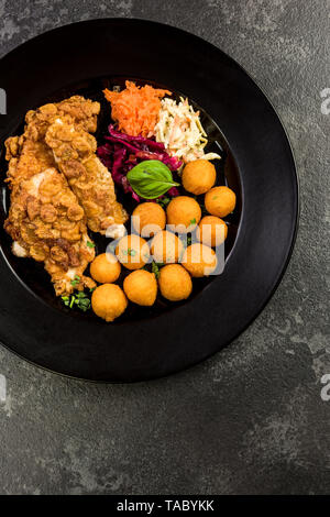 Fried chicken with potato balls and salad, restaurant serving portion. - Stock Image