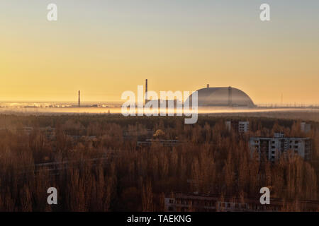 Cityscape view of Pripyat, Ukraine, inside the Chernobyl Exclusion Zone, with the Chernobyl Reactor in the background - Stock Image