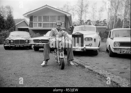 Elton John pictured at his home, sitting on a small motorbike in front of four of his cars. His cars include a Mercedes (2nd left) and a white Rolls Royce (3rd left)  Picture taken 4th April 1972 - Stock Image