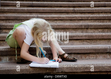 Young girl drawing in album, sitting on stone steps - Stock Image