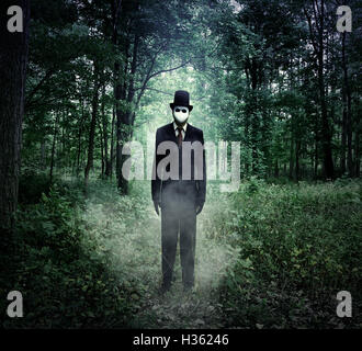 A scary tall man in a black suit is standing in the dark woods at night with fog for an evil halloween or fear concept. - Stock Image