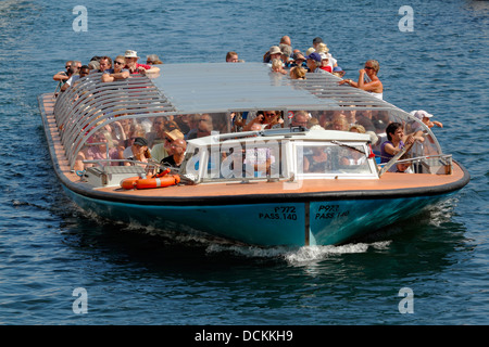 Netto-boat harbour cruise full of attentive tourists looking at the Royal Playhouse at Kvæsthusbroen in the - Stock Image