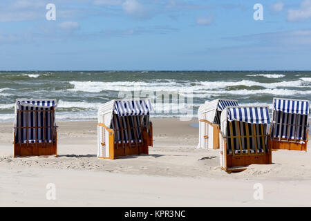 Beach chairs with sunscreens in Kolobrzeg in Poland can be seen on a sandy beach by the shore line on the Baltic - Stock Image