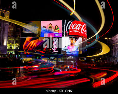 wild lights on the ever crowded Piccadilly Circus with car lights and advertising hoardings illuminating the night - Stock Image