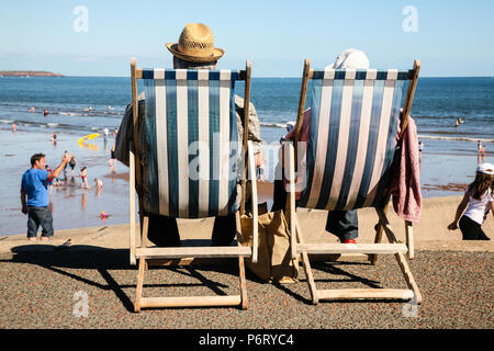 Older Hatted Couple enjoying the English Summer heatwave by the seaside in Traditional striped Deck chairs by the beach in Dawlish, England, Europe. - Stock Image