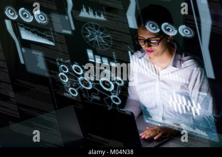 young businesswoman looking at futuristic graphical user interface. Internet of Things. Smart City. - Stock Image