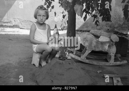 young girl sat on a stool in the garden next to a sandcastle and rocking horse 1930s hungary - Stock Image