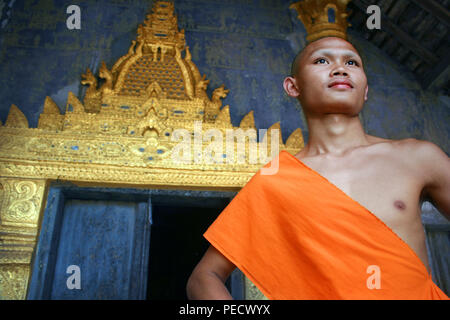 Stunning portrait of Buddhist novice young monk in Wat Xieng Thong monastery in Luang Prabang, Laos - Stock Image