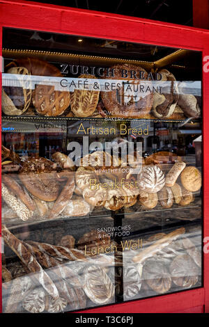 Shop window bread display featuring an assortment of produce for sale. - Stock Image