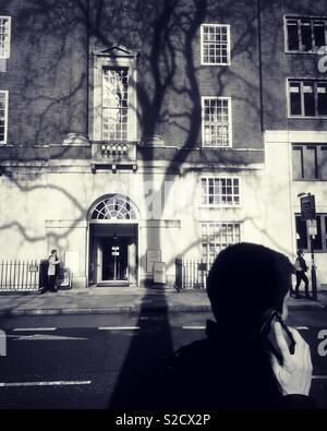 Man on phone in London street - Stock Image