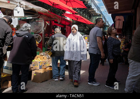 A Muslim woman in a hijab walks through a busy area on Roosevelt Avenue, under the elevated subway. Jackson Heights, Queens, New York. - Stock Image