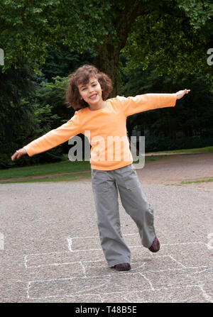 Little girl playing hopscotch in the local park - Stock Image