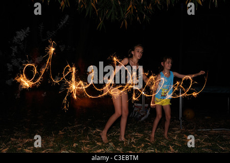 two children (12 years old, 9 years old) making patterns in the air with sparklers. - Stock Image