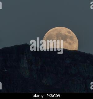 Full Moon Emerges Behind Mountain Ridge - Stock Image