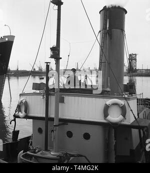 1950s, historical, steamboat tug, skipper manvouring his boat into the harbour. - Stock Image