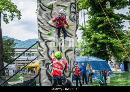 Male instructor working with young boy on climbing wall - Stock Image