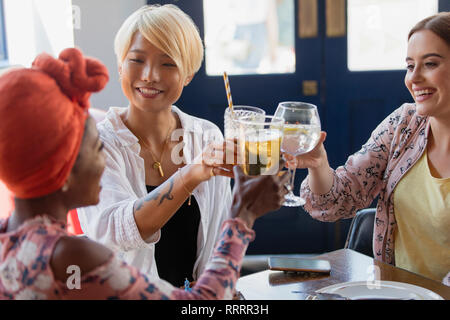 Young women friends toasting cocktail glasses in bar - Stock Image