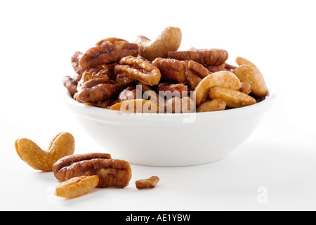 A bowl of mixed nuts with cashews almonds pecans with a white background cutout - Stock Image