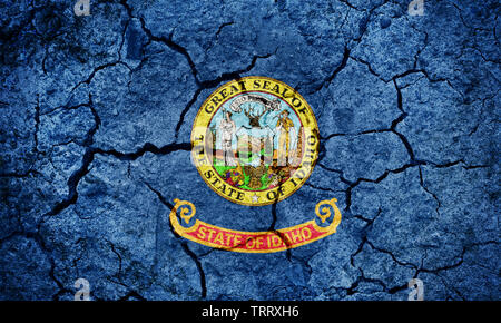 Flag of the state of Idaho on dry earth ground texture background - Stock Image