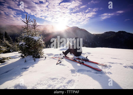 Skier looking at view while sitting on snowy mountain - Stock Image