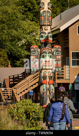 Sept. 17, 2018 - Ketchikan, AK: Three tourists wearing jackets viewing Chief Johnson Totem Pole on sunny day with local buildings in background. - Stock Image