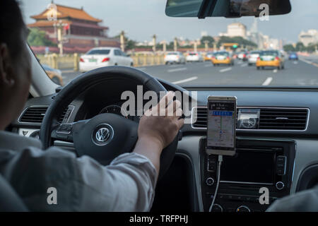 A DiDi express taxi past Tiananmen Gate in Beijing, China. - Stock Image