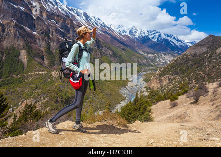 Beautiful Woman Traveler Backpacker Mountains Path.Young Girl Looks Right Way and Take Rest.North Summer Snow Landscape - Stock Image