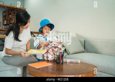 mom help her little girl preparing school stuff on her daughtes's backpack in the morning - Stock Image