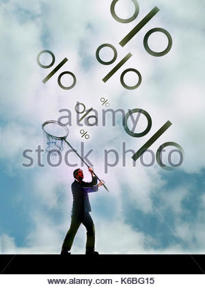 Businessman chasing percentage signs with butterfly net - Stock Image